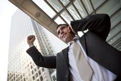 Glücklicher Stadt-Geschäftsmann, der auf Handy feiert Lizenzfreie Stockbilder