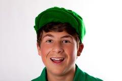 Glücklicher stattlicher Jugendlicher im Grün Stockfoto