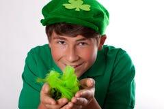 Glücklicher stattlicher Jugendlicher im Grün Stockfotografie