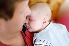 Glücklicher stolzer junger Vater, der kleine schlafende Babytochter, Familienporträt zusammenhält Stockbild