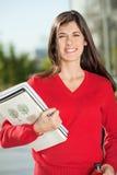 Glücklicher Student With Books Standing auf dem Campus Lizenzfreie Stockfotografie