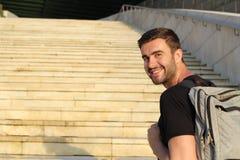Glücklicher Student, der auf dem Campus lächelt und oben vorangeht Stockfotografie