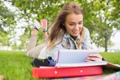 Glücklicher Student, der auf dem Gras studiert mit ihrem Tabletten-PC liegt Stockbild
