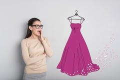 Glücklicher Student, der beim Betrachten des neuen Kleides aufgeregt glaubt Stockfoto