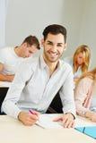 Glücklicher Student, der in der Klasse lernt Stockfotografie