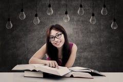 Glücklicher Student, der unter Glühlampen lernt stockbild