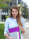 Glücklicher Student mit dem langen blonden Haar auf dem Campus Lizenzfreies Stockfoto