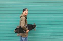 Glücklicher Student mit einem longboard in seinen Händen auf einem Farbtürkishintergrund, untersuchend die Kamera und das Lächeln stockfotografie