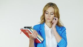 Glücklicher Student mit einem Stapel Büchern am Telefon Gefilmt am Studio auf einem weißen Hintergrund Kadettmädchen, welches die stock video
