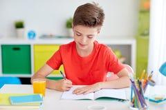 Glücklicher Studentenjunge, der zu Hause zum Notizbuch schreibt Lizenzfreie Stockfotos