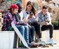 Glücklicher Teenager, der auf smarthphones spielt Stockfotos