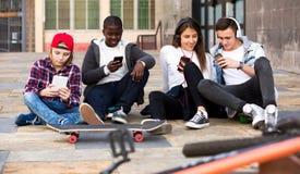 Glücklicher Teenager, der auf smarthphones spielt Stockbild