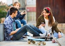 Glücklicher Teenager, der auf smarthphones spielt Lizenzfreies Stockbild