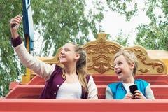 Glücklicher Teenager fährt auf das Karussell und macht selfie Stockbild