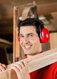 Glücklicher Tischler Carrying Wooden Plank auf Schulter Lizenzfreies Stockbild