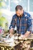 Glücklicher Tischler Marking On Wood sah bei Tisch stockfotografie