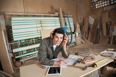 Glücklicher Tischler Working On Blueprint in der Werkstatt stockbilder