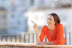 Glücklicher Tourist, der auf Seite in einem Balkon zeigt lizenzfreie stockfotografie