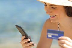 Glücklicher Tourist, der online mit Kreditkarte auf dem Strand zahlt lizenzfreies stockfoto