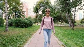 Glücklicher Tourist mit stilvollem Rucksack und Brillen gehend in grünen Park und Stadt während des Sommerabenteuers genießend stock video footage