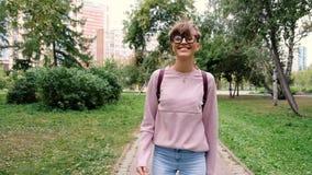Glücklicher Tourist mit stilvollem Rucksack und Brillen gehend in grünen Park und Stadt während des Sommerabenteuers genießend ju stock footage