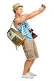 Glücklicher touristischer Mann, der die Weinlesekamera lokalisiert auf Weiß fotografiert Lizenzfreie Stockbilder