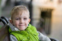 Glücklicher träumender schöner blonder Junge, der auf einer Bank sitzt Lizenzfreies Stockfoto