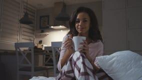 Glücklicher tragender Pyjama der jungen Frau, der mit Tee/Schokolade/der Kaffeetasse, lächelnd sitzt stock footage