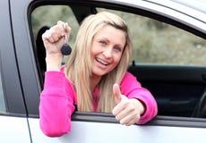 Glücklicher Treiber, der eine Taste zeigt, nachdem ein neues Auto gekauft worden ist Lizenzfreie Stockbilder