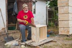 Glücklicher ukrainischer Bauer, der Bienenstöcke für sie auf dem Markt verkaufen und etwas Geld erwerben lässt Lizenzfreie Stockfotografie