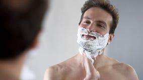 Glücklicher und überzeugter Mann, der Rasierschaum auf sein Gesicht bevor dem Rasieren setzt lizenzfreie stockfotografie