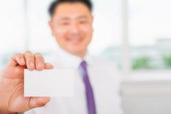 Glücklicher und erfolgreicher asiatischer Geschäftsmann gibt Ihnen eine Visitenkarte Lizenzfreies Stockfoto