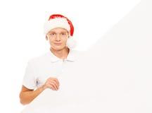 Glücklicher und hübscher Jugendkerl in einem Weihnachtshut und in einer Fahne Stockfotografie