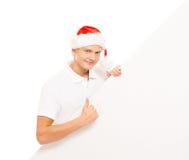 Glücklicher und hübscher Jugendkerl in einem Weihnachtshut und in einer Fahne Stockbild