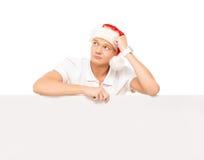 Glücklicher und hübscher Jugendkerl in einem Weihnachtshut und in einer Fahne Stockfoto