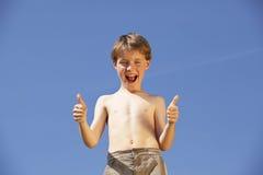 Glücklicher und lachender Junge, der oben Daumen aufwirft Stockfotografie