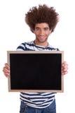 Glücklicher und stattlicher Mann, der einen schwarzen Vorstand anhält Lizenzfreie Stockbilder