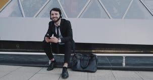 Glücklicher und Tanzengeschäftsmann hören Musik und Holding sein Telefon vor dem modernen Geschäftszentrum Rotes Epos stock video footage