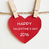 Glücklicher Valentinstag auf der roten Gewebeherzform, die am Stoff hängt Lizenzfreie Stockfotografie