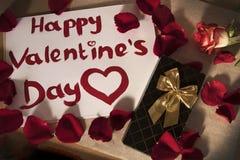 Glücklicher Valentinstag geschrieben in roten Lippenstift um rote rosafarbene Blumenblätter und eine Rose stockfoto