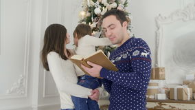 Glücklicher Vater, der eine Weihnachtsgeschichte während Mutter hält ihren netten Sohn vor dem Weihnachtsbaum liest stock video footage