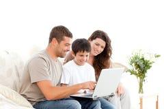 Glücklicher Vater, der etwas auf dem Laptop zeigt stockbild