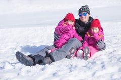 Glücklicher Vater, der im Schnee mit seinen zwei Töchtern sitzt Stockbild