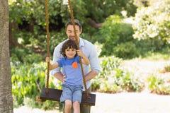 Glücklicher Vater, der Jungen auf Schwingen drückt lizenzfreie stockfotos