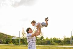 Glücklicher Vater, der Kleinkind in den Armen, werfendes Baby in einer Luft hält Konzept der glücklichen Familie, Vaterschaft Stockfotografie
