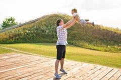 Glücklicher Vater, der Kleinkind in den Armen, werfendes Baby in einer Luft hält Konzept der glücklichen Familie, Vaterschaft Stockfotos