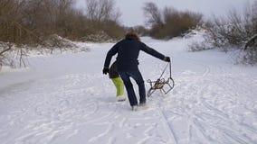 Glücklicher Vater, der mit seinem Sohnschlitten spielt Zusammen freuen sich sie und sind in der natürlichen Eisbahn froh Anziehen stock video