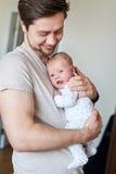 Glücklicher Vater, der neugeborenes Baby in seinen Armen hält Stockfoto