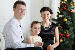 Glücklicher Vater, kleine Tochter mit Ring auf Finger und Mutter sitzen lizenzfreies stockfoto