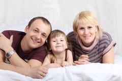 Glücklicher Vater, kleine Tochter und Mutter auf Bett Lizenzfreies Stockfoto